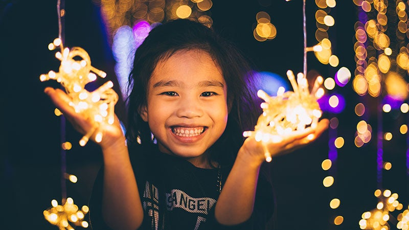 Little girl holding holiday lights